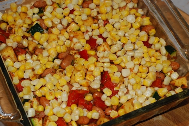 Beans and vegetable mix in a baking dish with a layer of corn