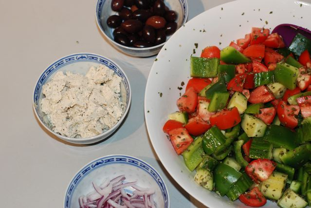 Greek Salad with bowls of olives, red onion ansd soy feta