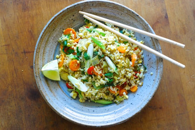 Thai Curry Tofu Fried rice pictured from above garnished with a wedge of lime and served with chop sticks