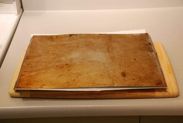 Put a parchment-lined cookie sheet over the polenta round on the cutting board and flip again