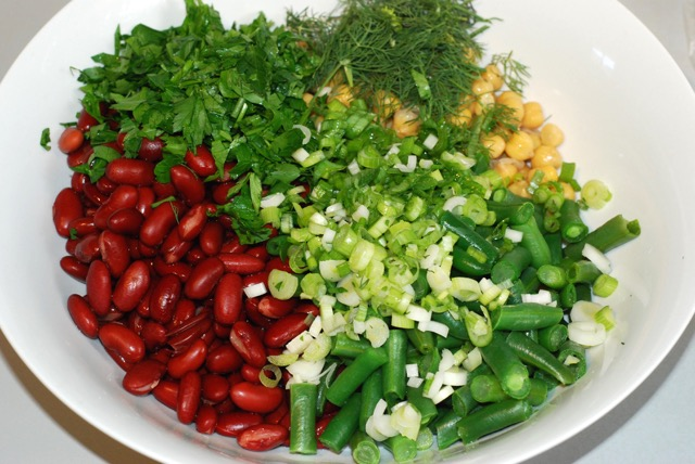 Chickpeas, kidney beans, green beans, parsley, dill, green onion in a bowl ready for dressing