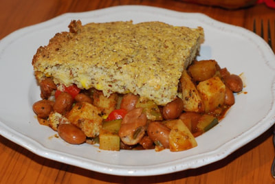 A slice of Quick Cornbread Casserole pictured from the side showing the top layer of cornbread with the seasoned bean and vegetable layer underneath