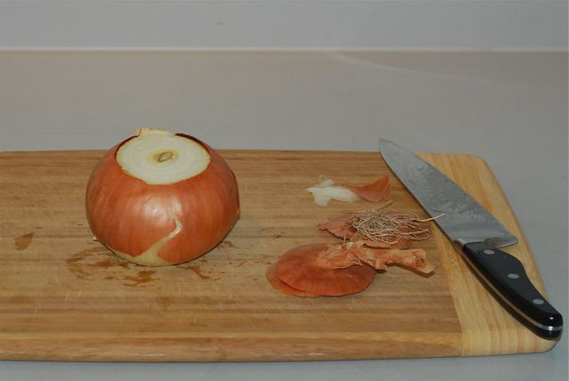 Onion on  a cutting board, stem and root ends removed