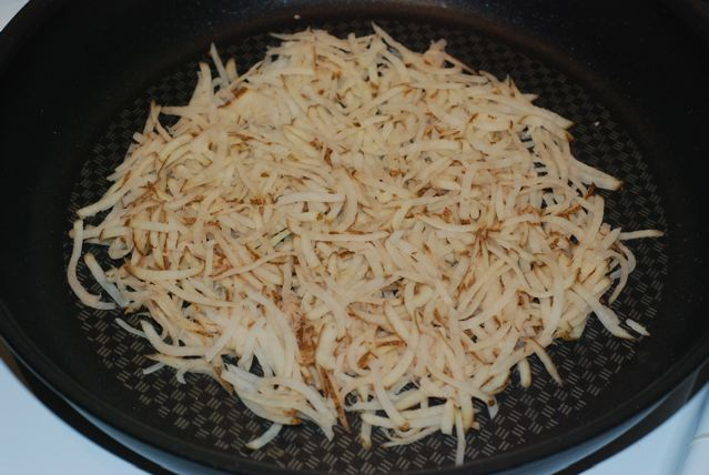 Shredded potato spread out evenly in the non-stick pan