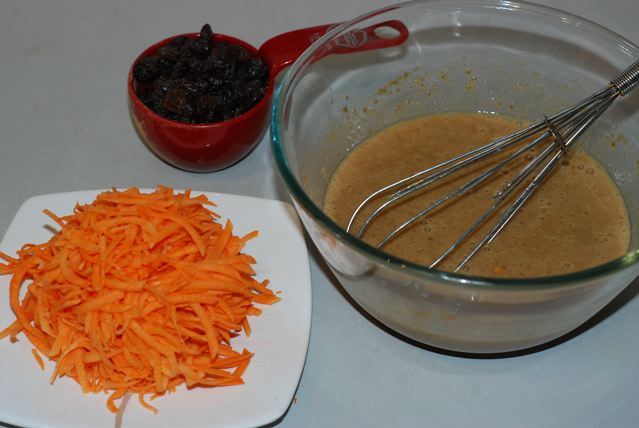Wet ingredients with shredded sweet potato and raisins