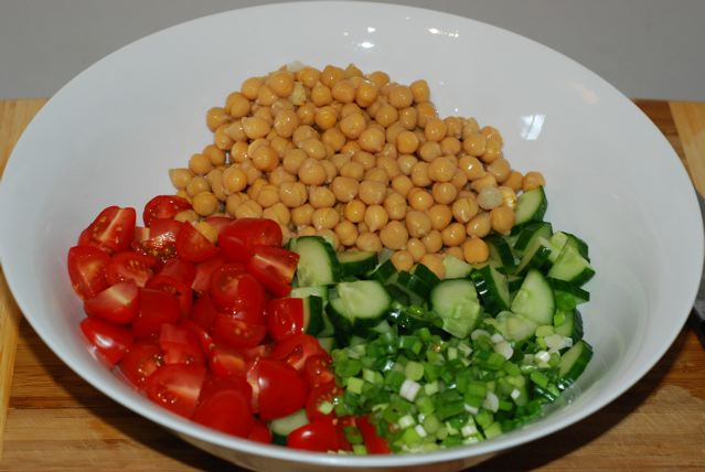 Chopped cucumber, green onion, tomatoes and chick peas ina salad bowl