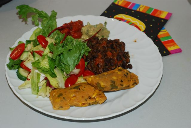 Lunch is served, 2 tamales with seasoned black beans and a big salad